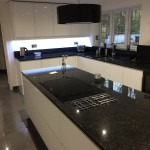 handleless white gloss with angola black granite
